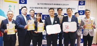 協定書を持つ桐ケ谷市長(前列右から2人目)と砂永支社長(同3人目)と、関係者たち