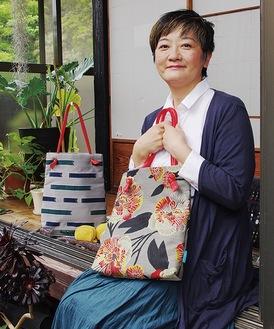 デザインしたバッグを手にする佐野さん