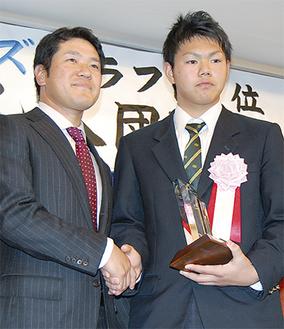 田代監督から記念品を受け取った高橋選手(右)
