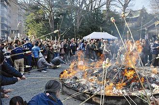 立ちのぼる炎で団子を焼く参拝者ら