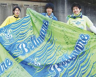 寄せ書き入りの大旗を手にする(左から)宮本さん、小川さん、古川さん