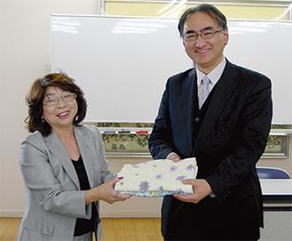 タオルを手渡す飯塚会長(左)