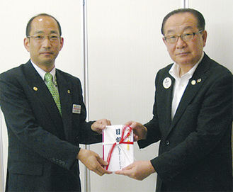 目録を手渡す川口会長(左)