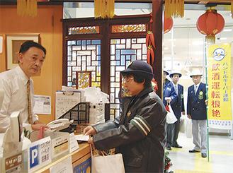 ボランティアと警察署員が湘南台の飲食店にグッズなどを配り、飲酒運転根絶の啓発活動を行った