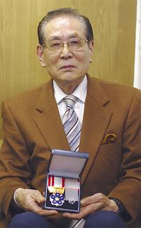 受章メダルを手にする神藤氏