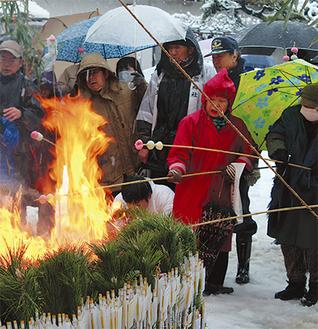 雪が降る中、焚上場の火で団子を焼き無病息災を願った