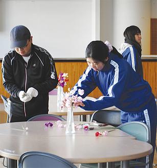 自分たちで栽培、収穫したスイートピーを校内ラウンジの花瓶に生ける生徒ら