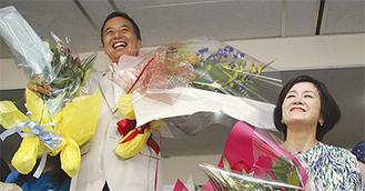 島村氏(左)は支持者から花束を受け取り笑顔(右は妻の奈津子さん)