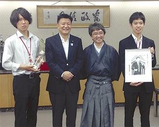 最優秀賞に輝いた初鹿敏也さん(左)と佐藤久太さん(右)16日の授賞式で、総務大臣らと