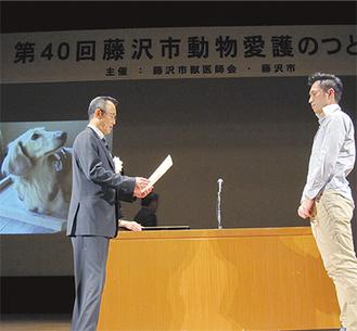 長寿犬猫の飼い主を表彰した西川会長スクリーンには若々しい長寿犬の写真も映し出された