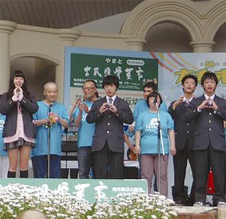 障害者とともに手話コーラスで歌う部員たち