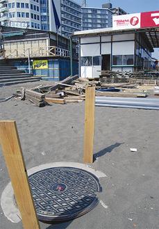 シーズンに向け建築が進む砂浜には下水管のマンホールが設置されている