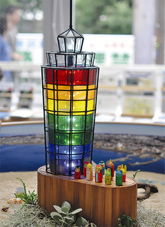 虹色に輝く灯台のオブジェ(高52×幅17cm)。写真はデザイナー市川勝典さん(鵠沼海岸)、土台と人形は作家スタジオ ナナホシさん(鵠沼桜が岡)