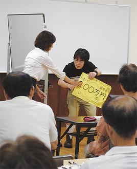実例をもとに振り込め詐欺の手口を演じる田畑さん(奥左)と遠間さん(中央)