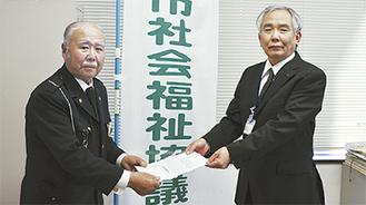 冨田会長(左)から大橋常務理事に手渡された