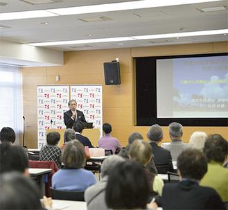 口腔がんについて講演する石川氏、会場には約80人が集まった