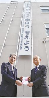 懸垂幕の下で笑顔の豊島署長(左)と山田会長