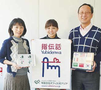 アプリ画面を手にする(左から)開発者の高橋千鶴子さんと島津さん、高橋代表
