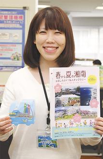冊子と景品のペンケースを手にする市観光課職員