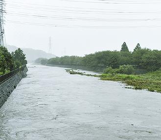 水位が増し、茶色く濁った水が流れる引地川