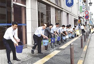 最上会長(左から2人目)、信金職員らが一斉に水を撒いた