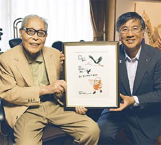 色紙を持つかこさん(左)と鈴木市長=藤沢市の自宅で