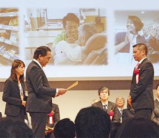 黒岩知事から表彰を受ける田代鉄也副理事長