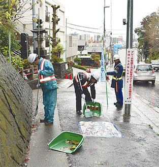 雨の遊行寺坂で清掃を行う組合員