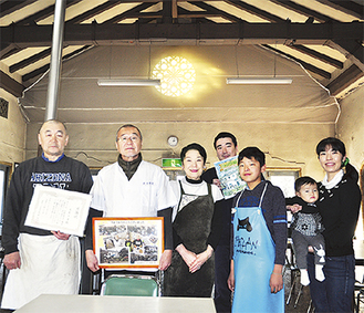 店主の古郡一家。(左から)弟の泰彦さん、治男さん、啓子さん、その子どもと孫ら県職員から送られた表彰状と写真を手に