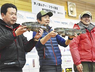 釣り上げた魚を手にする榊原さん(中央)