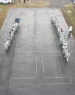 生徒たちと、完成した「藤工」の文字