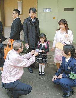 入学式に向かう親子に防犯グッズを手渡した