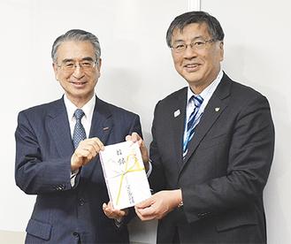 鈴木市長へ寄付を手渡すアズビル山武財団の小野木理事長(左)