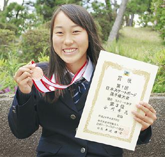 メダルと賞状を手にする小川さん