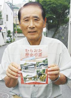 改訂した冊子を手にする菅井部会長
