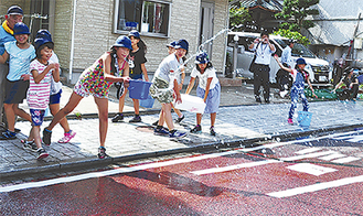 バケツで水を撒く児童