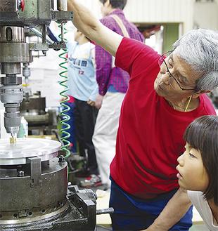 機械を操作して教える倉田さん