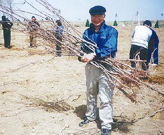 苗木を持つ馬渕豊さん