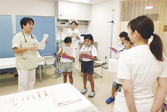 子どもたちに医師の仕事について説明する道海医師。子どもたちはメモを取るなどして、真剣な表情で学んでいた