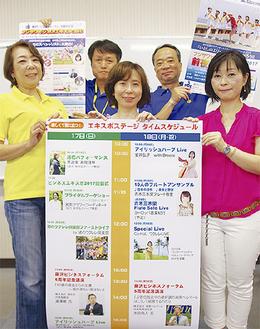 イベントポスターを掲げるメンバー