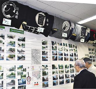 前田さんによる4枚の定点観測写真を見ながら、鵠沼の街並みの変遷を語る来場者ら。天井には一面に半纏が展示されている。