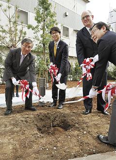 苗木に土をかける鈴木藤沢市長、田上長崎市長(左から2番目)ら