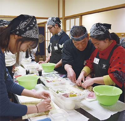 巻物を指導する板長の池田さん(右から2人目)