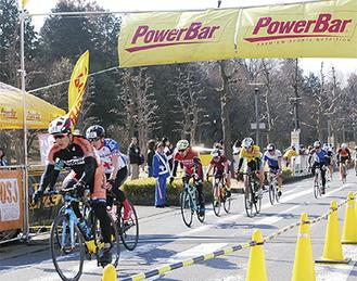 自転車でコースを疾走する参加者ら