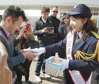 会場に集まった人に啓発物を手渡す富田さん(右)
