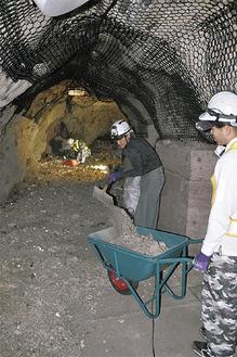台風で流れ込んだ石や砂を搬出する作業員ら(=19日、江の島岩屋)