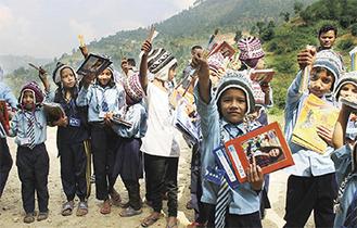 寄付されたノートや鉛筆を手に喜ぶネパール山岳地帯の子どもたち(平綿さん提供)