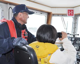 操縦を教える海保員と望遠鏡をのぞく参加者