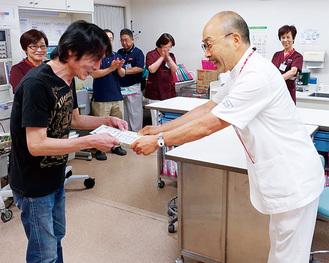 退院する男性に証書を渡す山中院長(右)