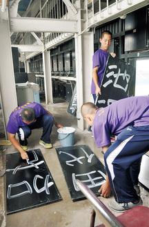 試合中、手際よく選手の名を書き入れる部員ら